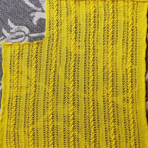 Knitted lace and cable rectangle with an opening for neck
