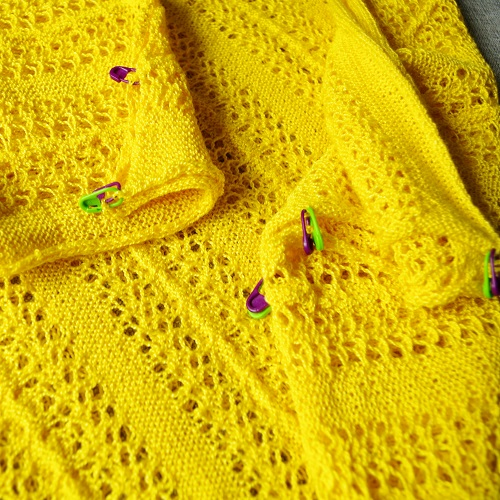 Sewing a big yellow poncho with lace and cables